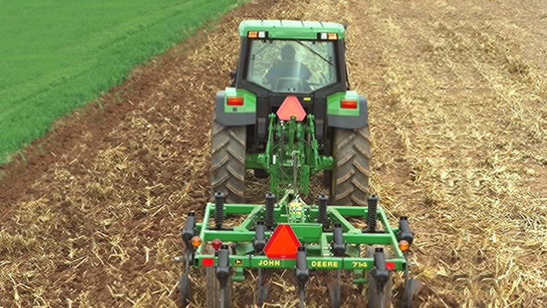 Man pulls a John Deere mulch tiller behind a John Deere tractor.