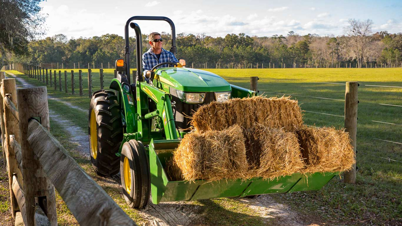 John Deere Tractor carrying hay bales