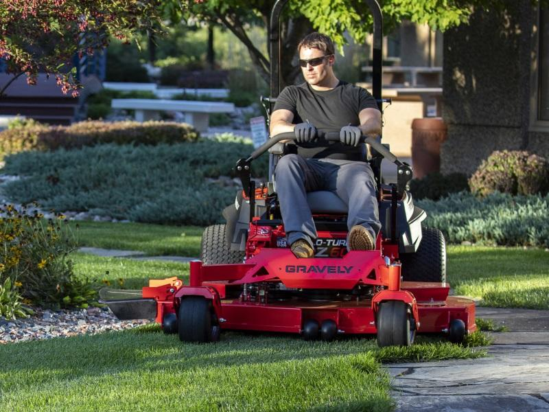 Man mowing his lawn with a Gravely zero turn mower