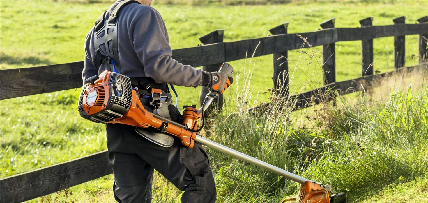 Man uses Husqvarna brush cutters near a wooden fence