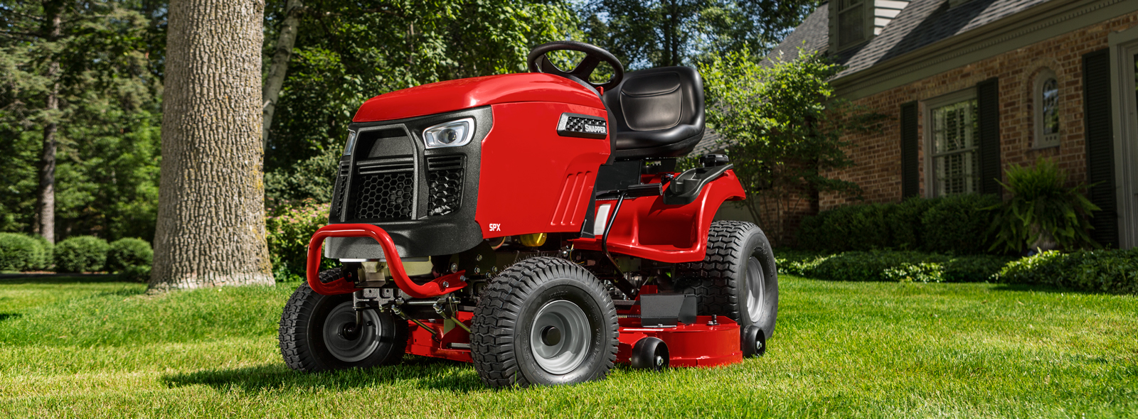 Snapper riding mower sitting idle in front of a house.