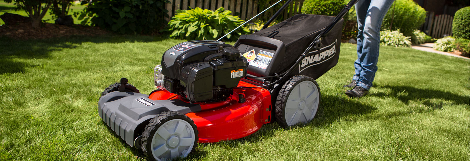 Close up side view of a red Snapper push mower on green grass.