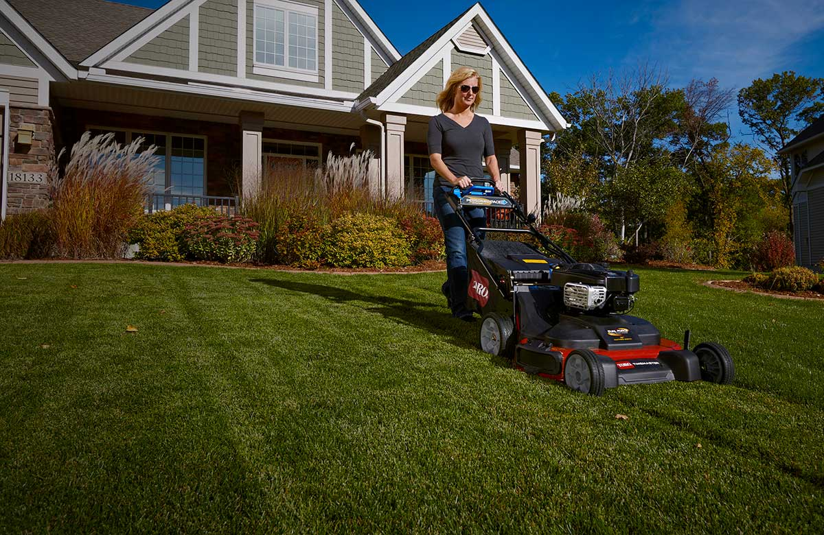Woman mowing her lawn with a TORO walk behind lawn mower making her lawn look great
