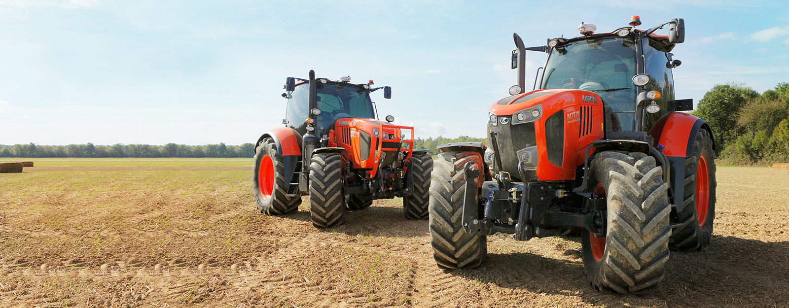 Two Kubota tractors parked in freshly cut field