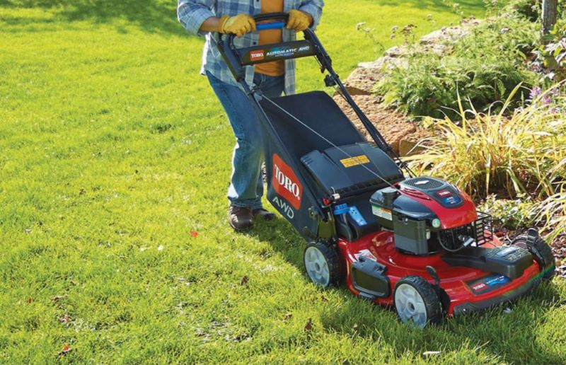 Person pushing a Toro Walk-Behind Lawn Mower which is cutting the emerald grass around a flower bed.