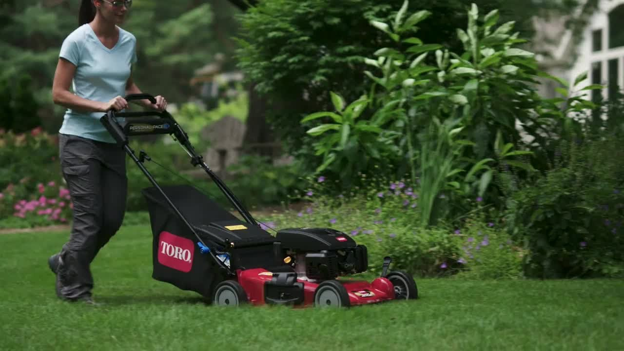 Woman mowing the lawn with a Toro mower