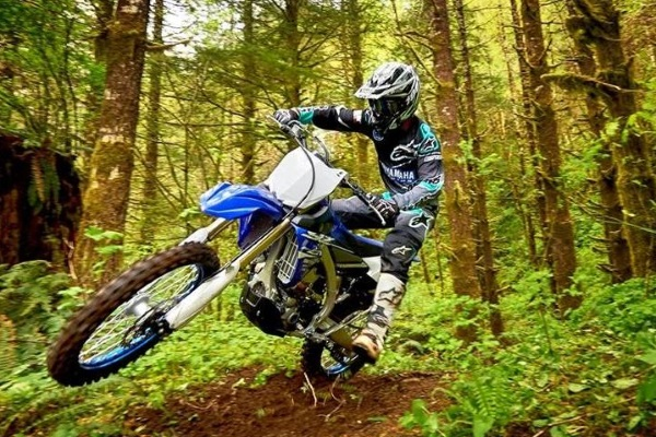 a man riding a 2018 Yamaha YZ450FX on the forest