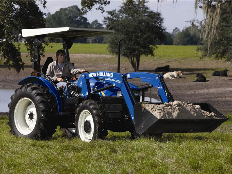 2017 New Holland 55 AWD tractor moving dirt in a cow pasture with bucket attachment