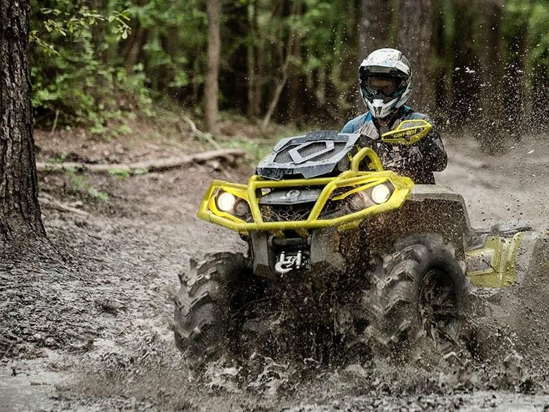 2019 Can-Am® Outlander™ X® mr 1000R ATV kicking up mud on forested trail
