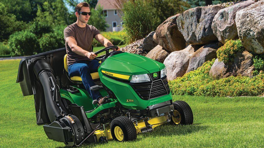 Man riding a John Deere riding mower on a green lawn