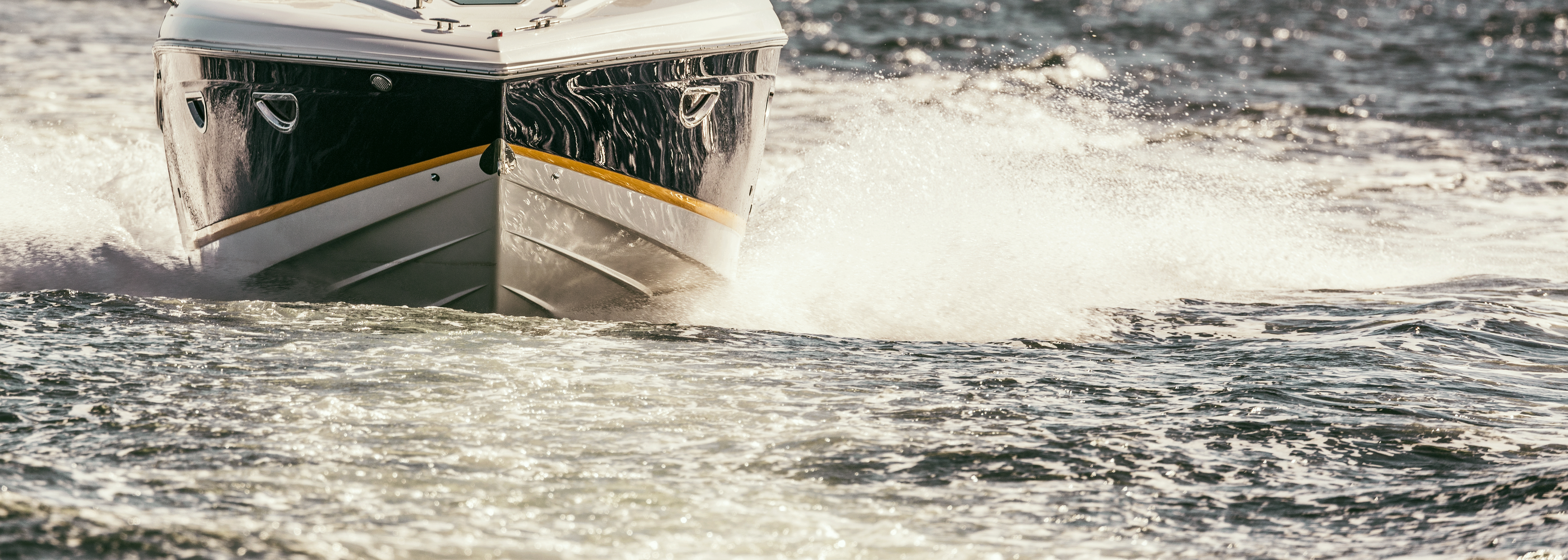 A fast blue and white boat with yellow trim moving at speed across choppy water and leaving a wake.