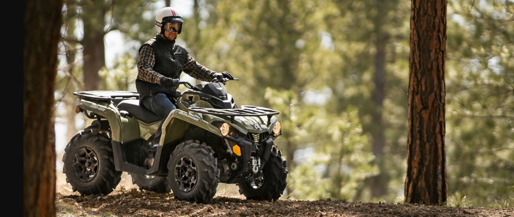 Can-Am Outlander ATV driving through a forest