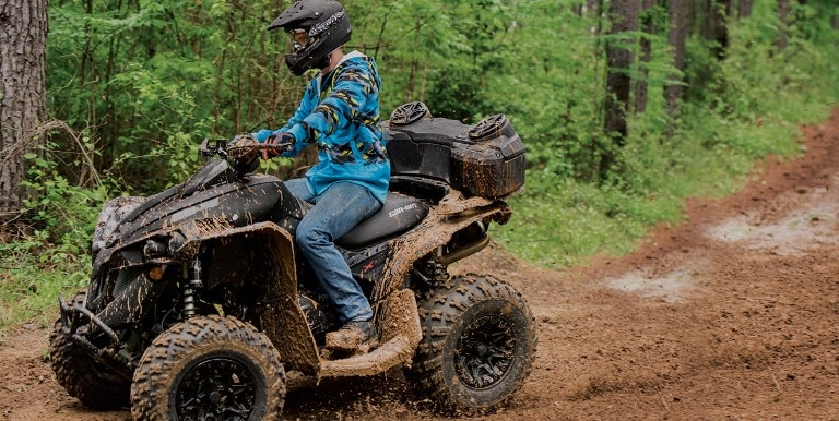 Woman on a Can-Am Renegade traveling on a dirt path through trees.