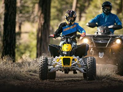 Young kid out on a ride on a Can-Am youth atv with their parent.