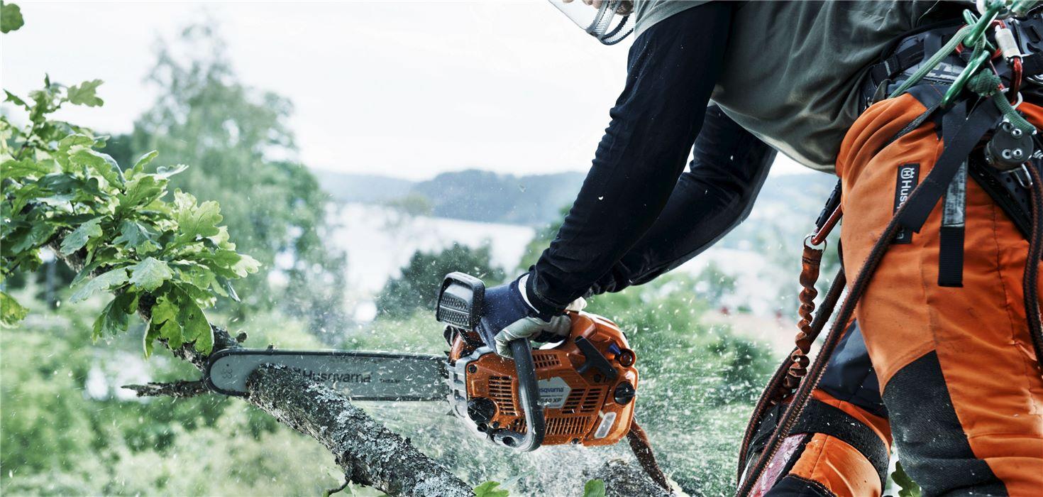 Man using Husky chainsaw.