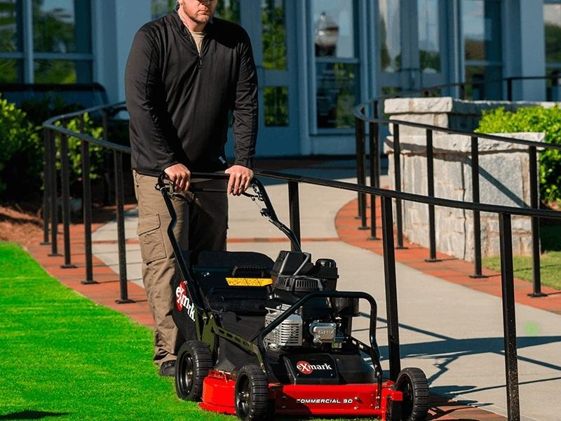 Man mowing his lawn with a Exmark walk behind mower cutting his grass
