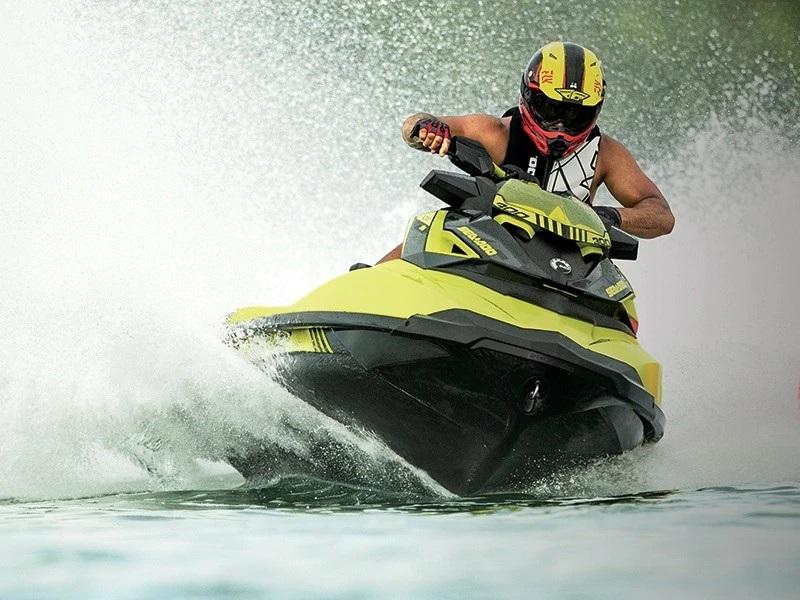 Man wearing yellow helmet turning on a neon yellow and lava grey 2019 Sea-Doo® RXP®-X®
