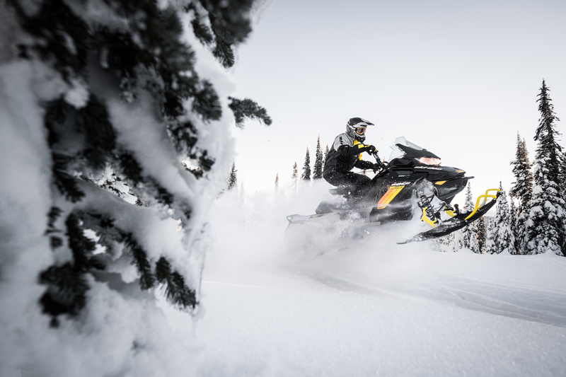 2019 Ski-Doo® MXZ sled jumping a snow berm with a snow covered evergreen in the foreground