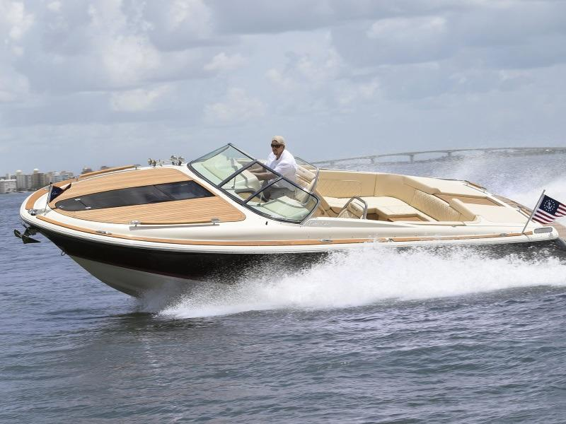 A 2019 Chris-Craft Corsair 30 boat in a turn displaying its topside teak wood panneling