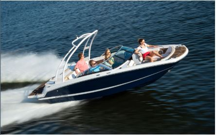 Family of four relaxing on a speeding Four Winns HD 200 deck boat.