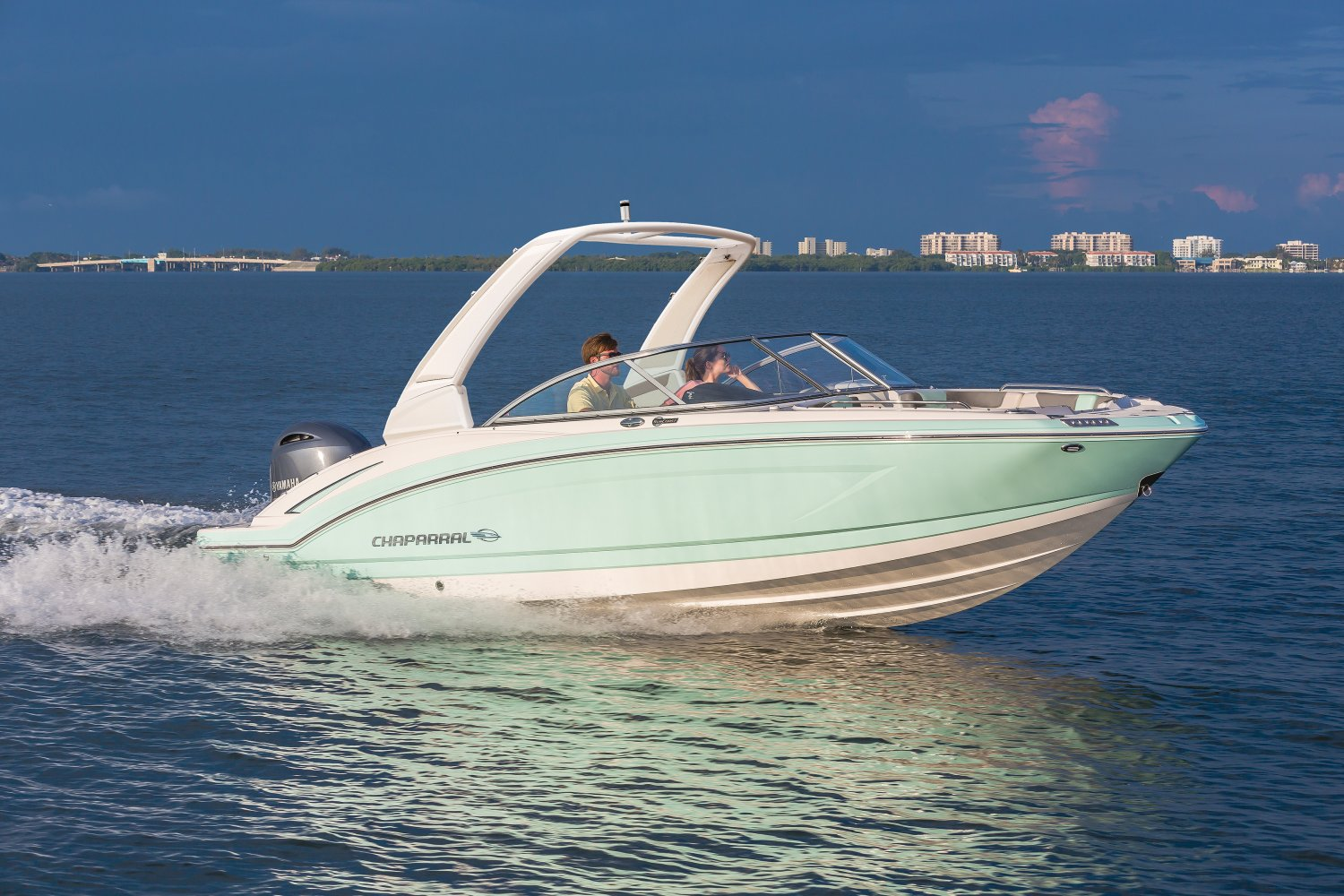 Couple cruises on the water in a Chaparral Suncoast 230 deck boat.