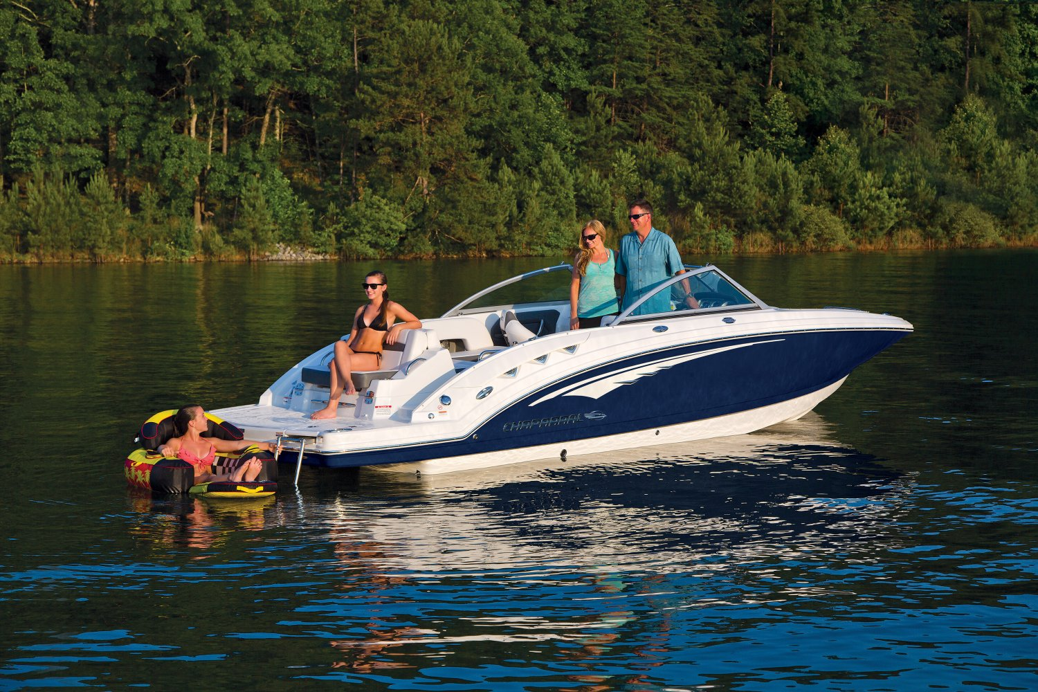 Family on a Chaparral wakeboard boat relaxing with a girl on a floatie