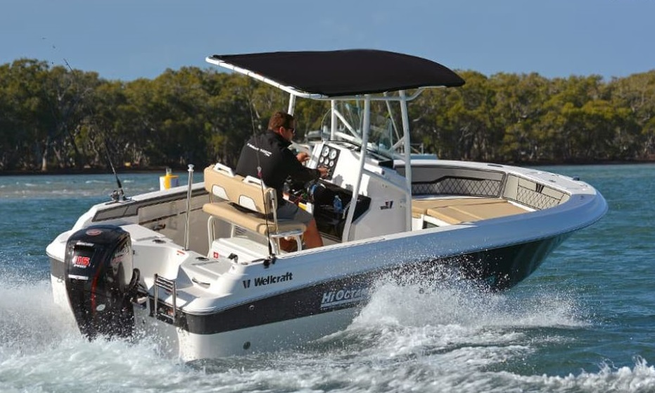 A man takes a turn on a Wellcraft center console boat.