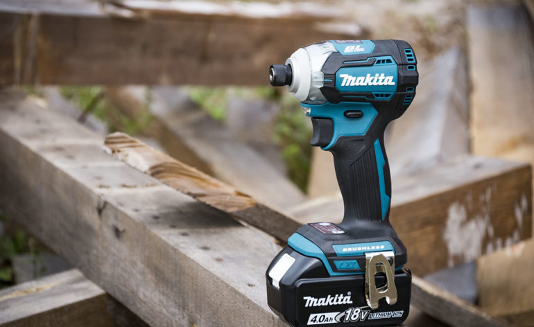 Shot of a Makita power tool sitting on a wood pile