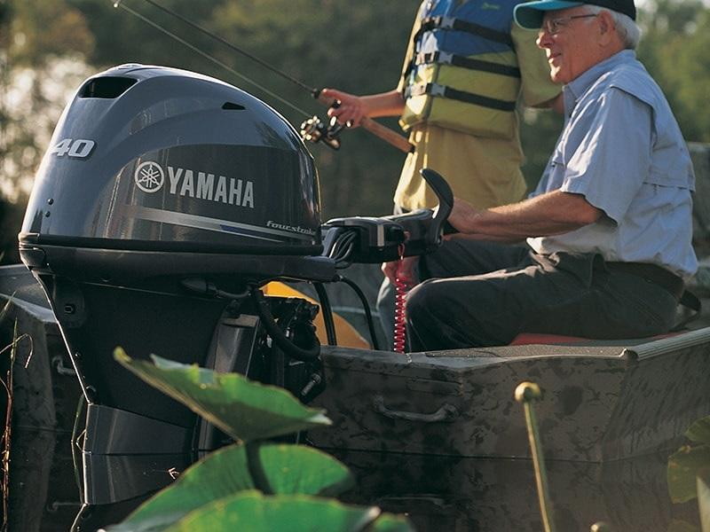 Father and son fishing off boat powered by a Yamaha Outboard Motor