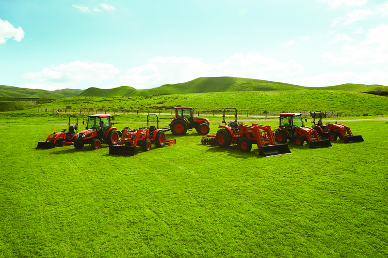 KIOTI® tractor models displayed in a green field with rolling hills in the background