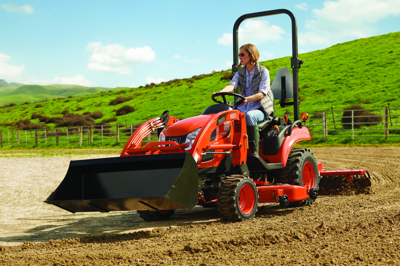Woman driving KIOTI CS2210 Tractor with rake in pasture