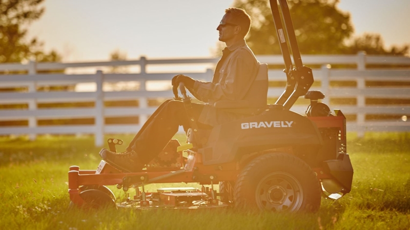 Man Mowing Field at Sunset With Gravely Zero-Turn Mower