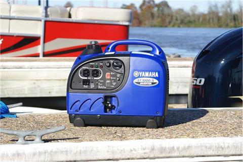 Yamaha generator sitting on the dock near a boat at a marina