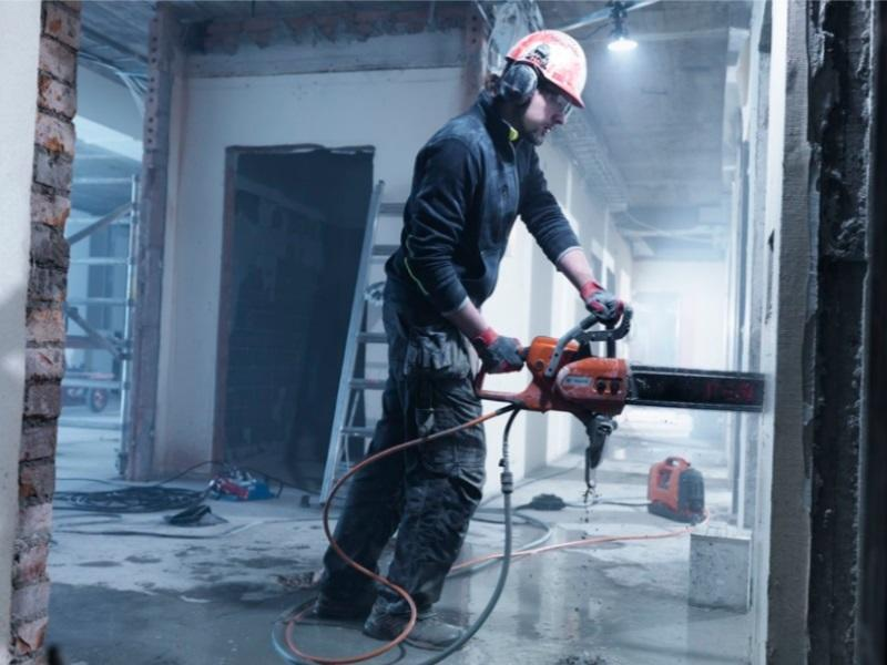 Man using a Husqvarna chainsaw to do work on a construction site