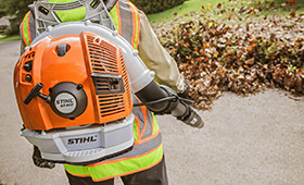 Man using a STIHL backpack blower to blow leaves