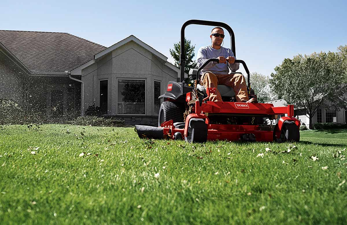 Man on a Toro lawn mower cutting the grass