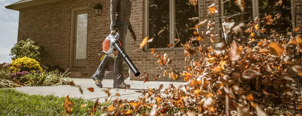 Woman using a STIHL leaf blower to clear a walkway