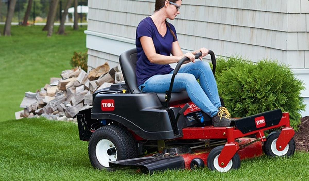 Cutting the grass on a Toro lawn mower.