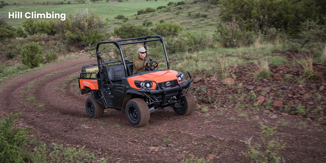 Man using a Kubota Sidekick utility vehicle to climb hills