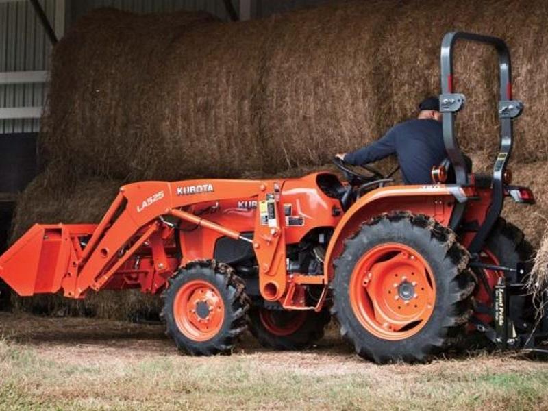 Man towing hay in a 2019 Kubota L3901 4WD