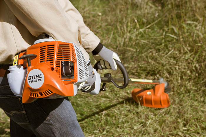 Person cutting down tall grass with a string trimmer