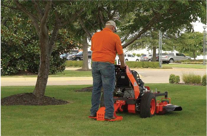 cutting grass on a stand behind mower