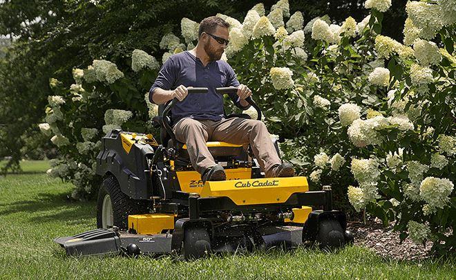 Man using a Cub Cadet lawnmower cutting the grass near a flower bed.