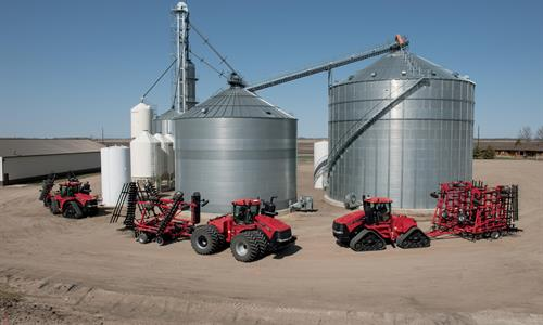 Collection of Case IH ag equipment parked around a silo.