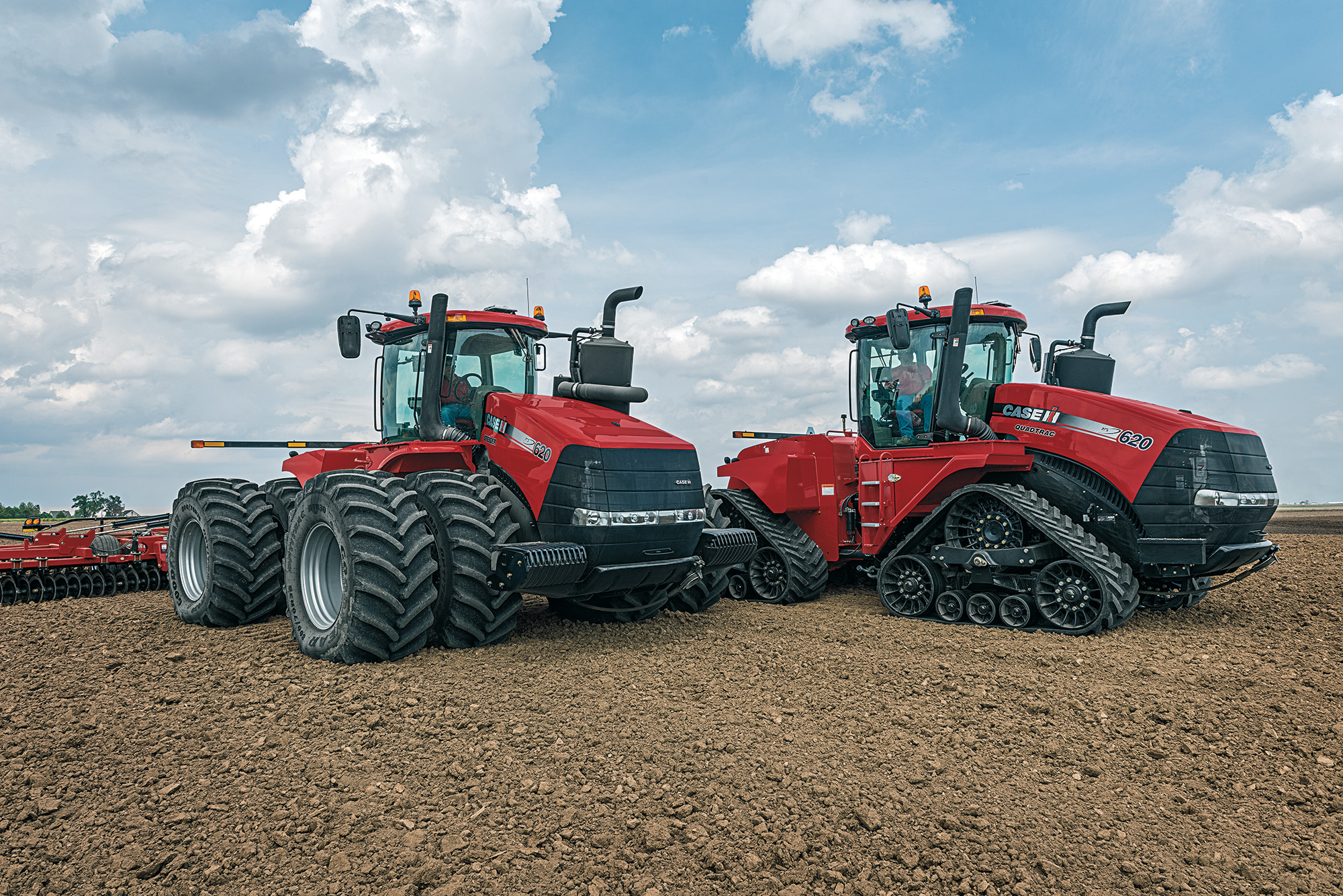 Two Case IH tractors parked side by side on a field.