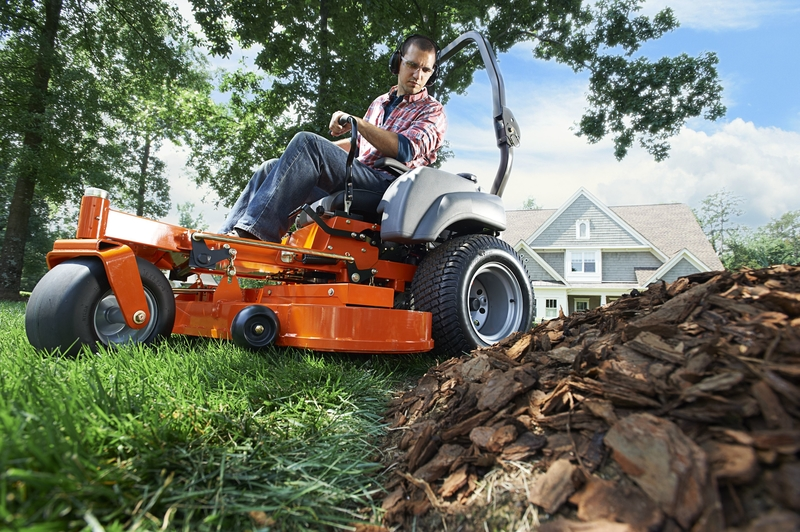 Husqvarna® M-ZT61 zero turn mower effortlessly navigating the edge of a yard bordered by bark chips