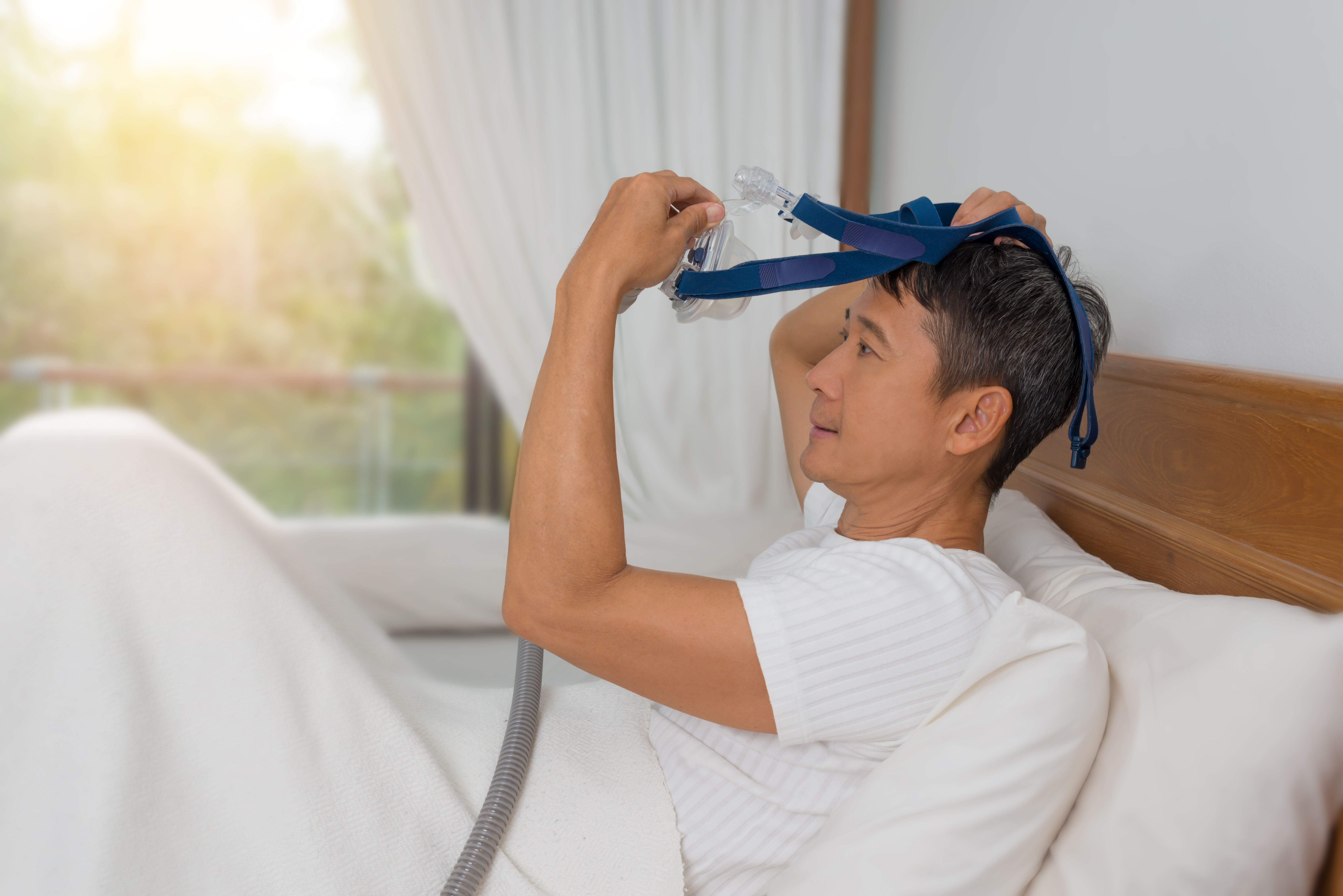 Man removing CPAP Mask while laying in bed