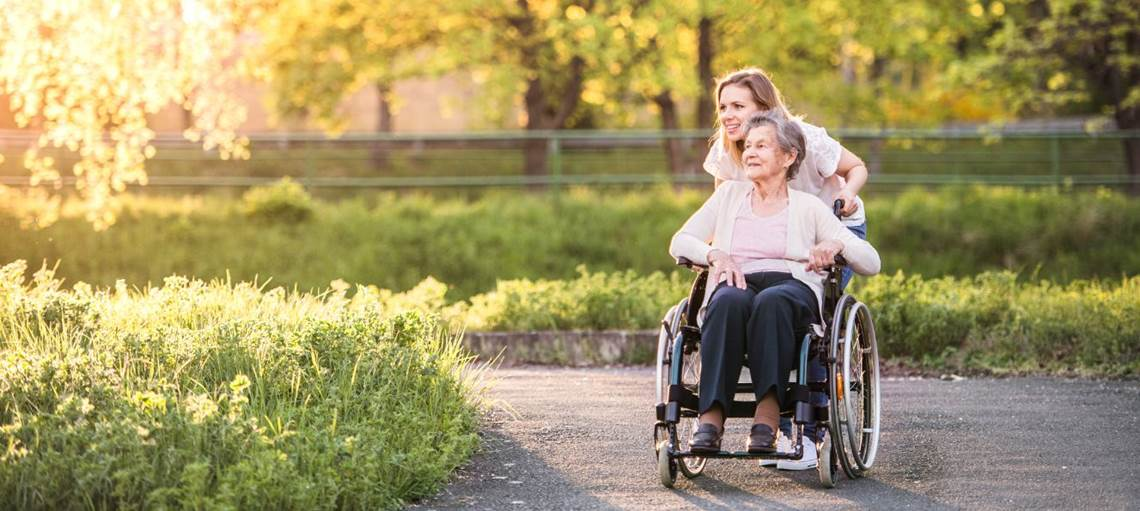 Lady pushing grandmother in wheelchair