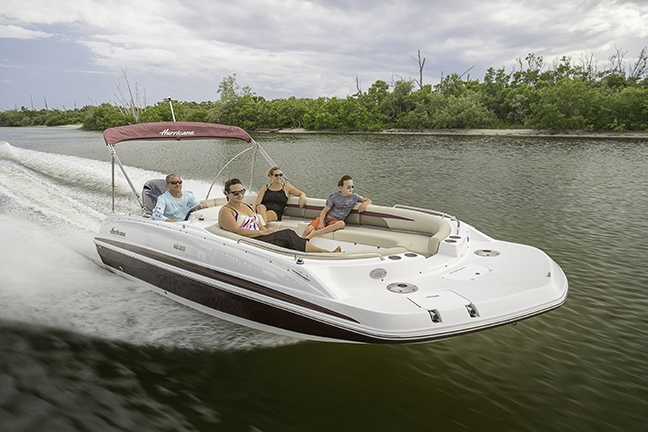 Family of four relaxing on a speeding Hurricane deck boat.